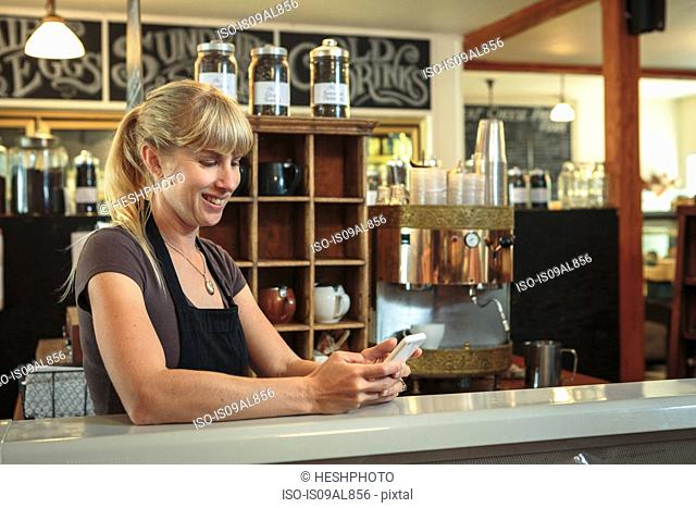 Female shop assistant texting on smartphone in country store cafe