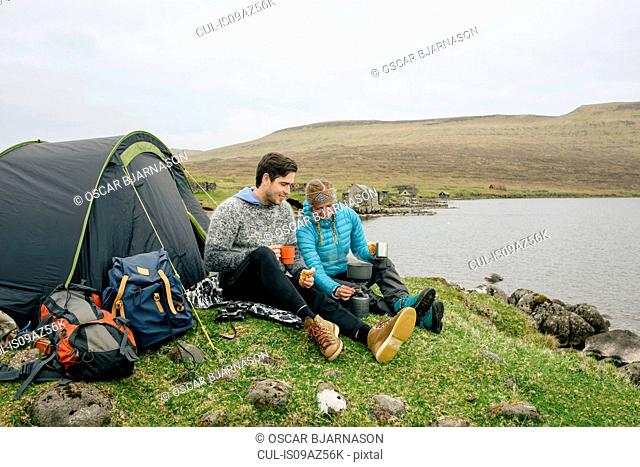 Campers relaxing beside tent on hill, Vagar, Faroe Islands