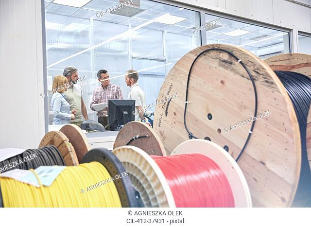 Supervisors talking in office behind spools in fiber optics factory