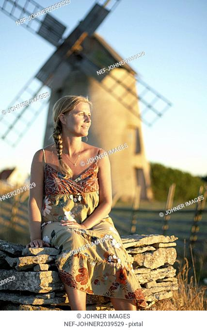 Smiling woman, windmill on background