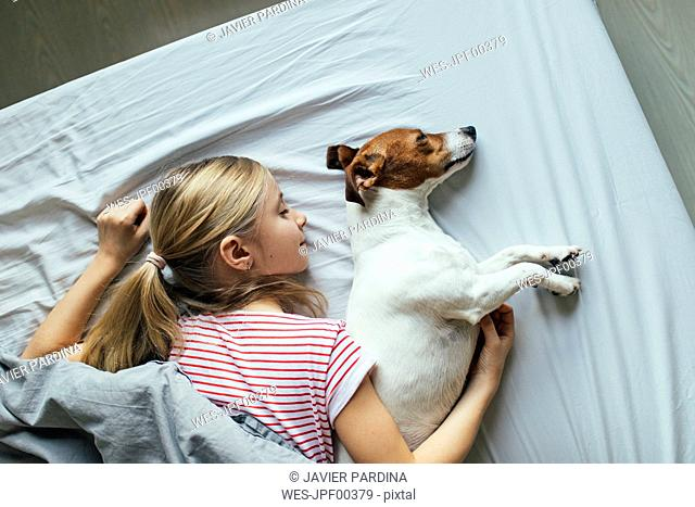 Blond girl lying on bed with her dog sleeping, top view