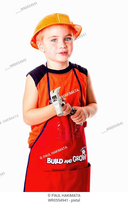Little Caucasian boy dressed in orange with construction helmet and apron with pockets, holding a hammer, isolated