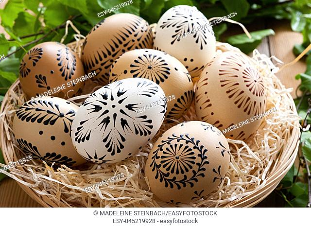 Easter eggs painted with wax in a basket, with birch branches in the background