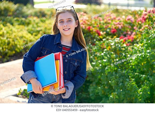 Blond kid student girl with notebook and backpack in the park back to school