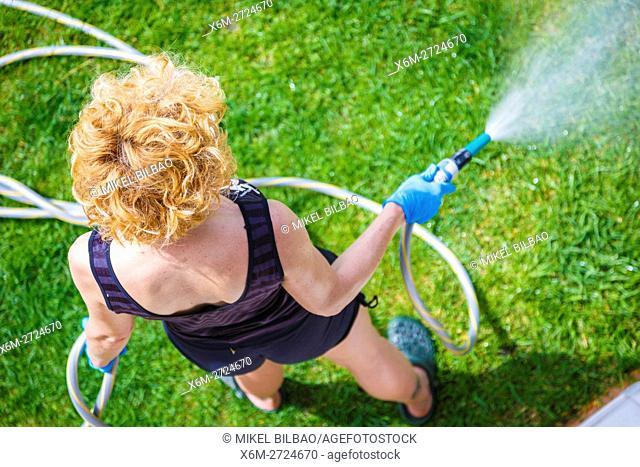 Woman irrigating a garden