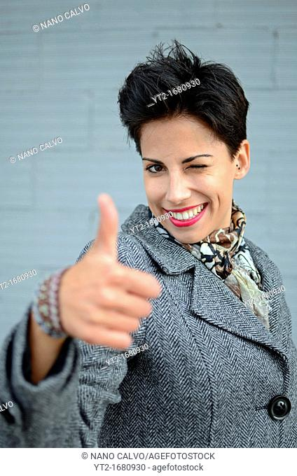 Attractive short haired young woman makes Ok sign with hand