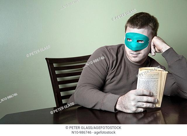 Young man wearing a mask and holding a book