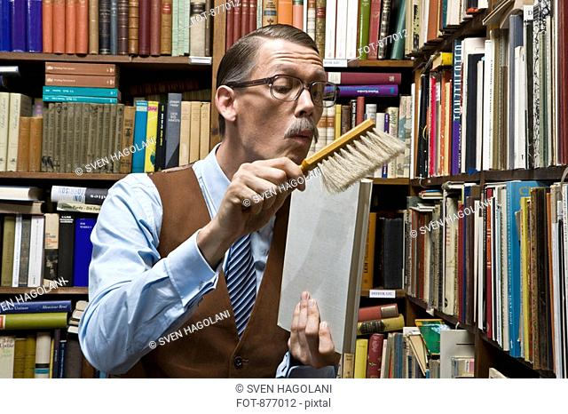 A man using a dust brush on a book