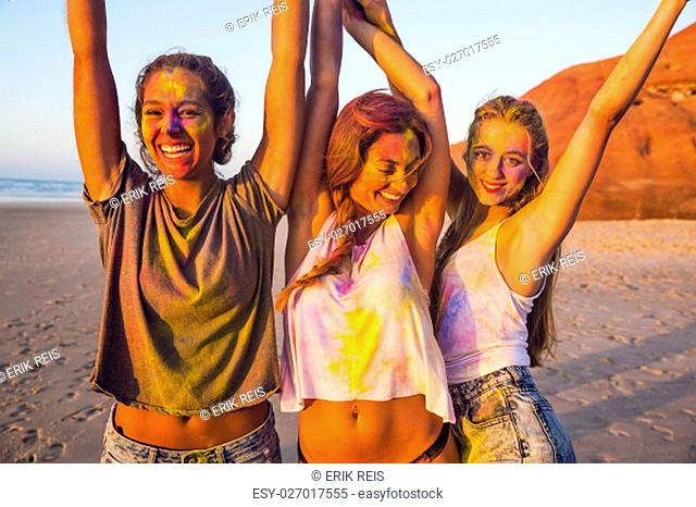 Teenagers playing with colored powder on the beach