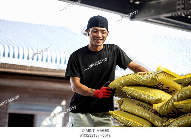 Japanese farmer wearing black cap standing next to stack of yellow plastic sacks, smiling at camera