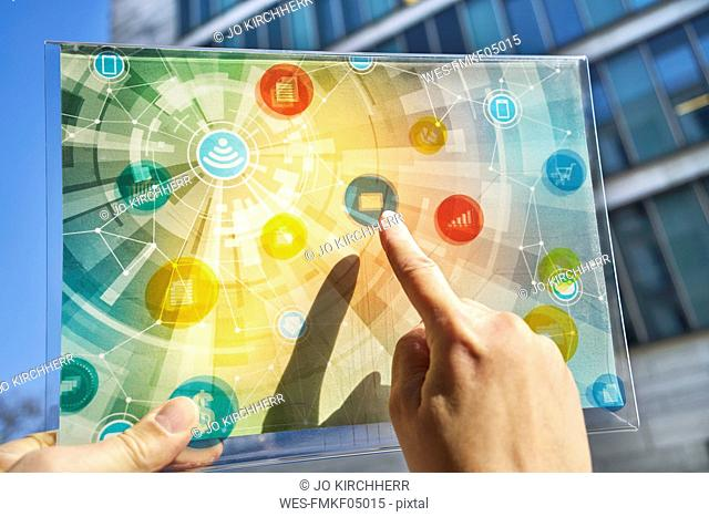 Hand holding futuristic device with digital icons