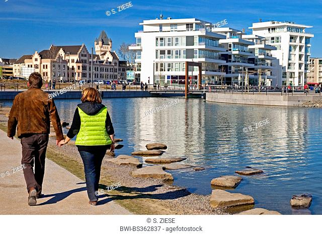 two people walking on the Phoenix Lake front, Hoerde Castle and medical center in background, Germany, North Rhine-Westphalia, Ruhr Area, Dortmund
