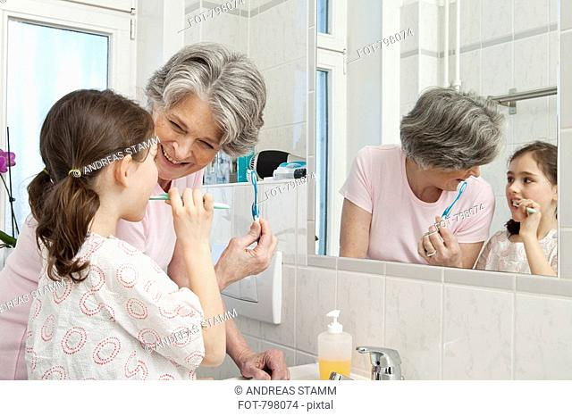A grandmother helping her granddaughter brush her teeth