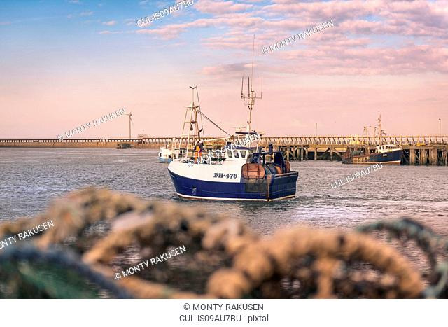 Fishing trawler in port at dawn