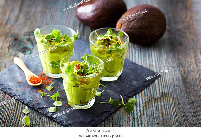 Glasses of avocado cream with chili flakes, cress and parsley