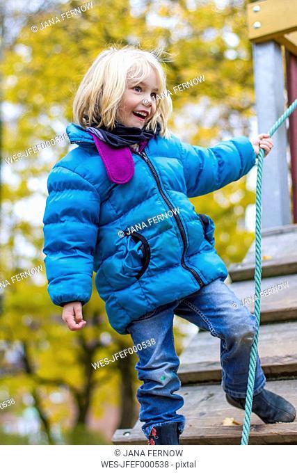 Happy little girl standing on playground equipment