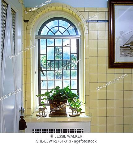 ARCHITECTURAL DETAILS: Detail of arched leaded glass window in bathroom of old mansion, cream colored tile on walls, potted house plant on window sill