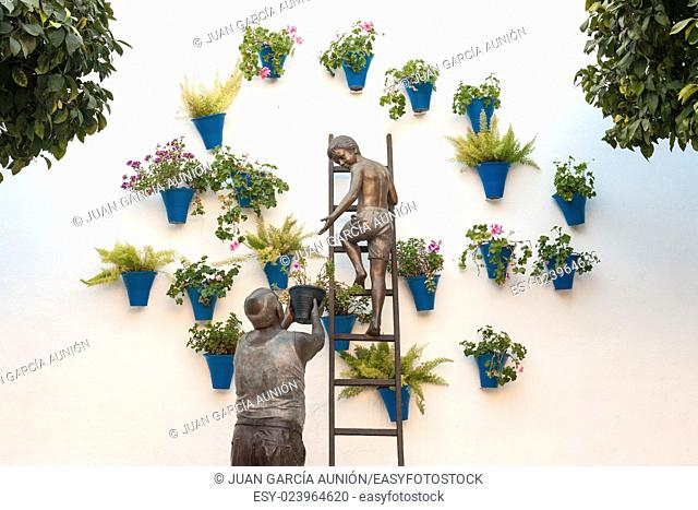Sculptural ensemble representing a granny and his grandson placing flowerpots on the wall