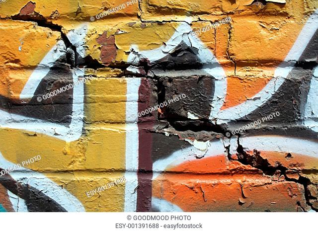Bright graffiti on a cracked brick wall