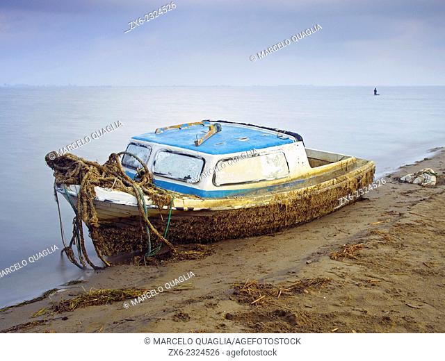 Abandoned small fishing boat after a storm at Alfacs bay. Trabucador Isthmus. Ebro River Delta Natural Park, Tarragona province, Catalonia, Spain