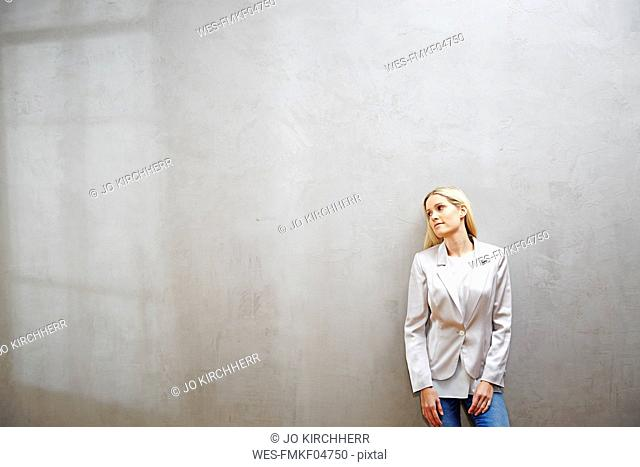 Relaxed businesswoman standing in front of grey wall