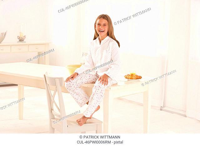 Smiling girl sitting on breakfast table