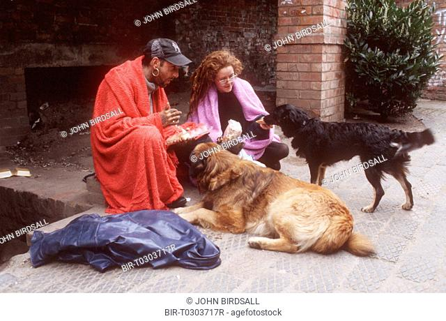 Homeless couple sitting in street wrapped in blankets feeding pet dogs
