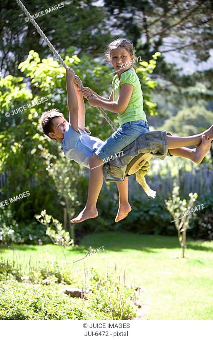 Boy and girl 8-10 swinging on garden rope swing, smiling, side view, portrait