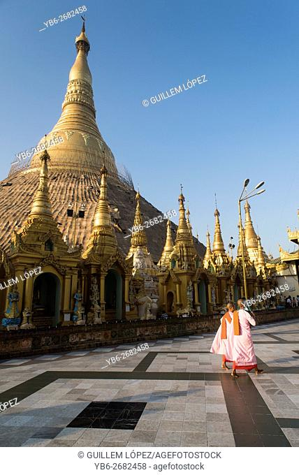 Two Buddhist nuns walk by Shwedagon pagoda, Yangon, Myanmar