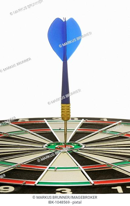 Blue dart exactly in the centre of a dartboard