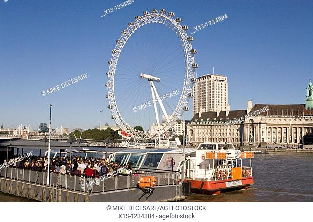 Along the Thames with water taxis in foregound and London Eye on the opposite shore