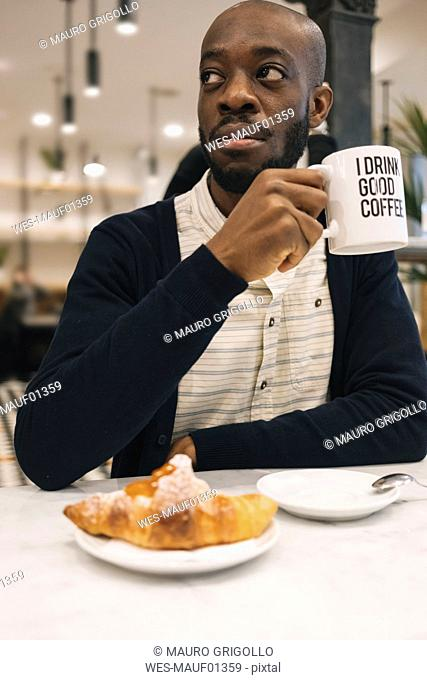 Man with croissant and cup of coffee in a cafe looking around