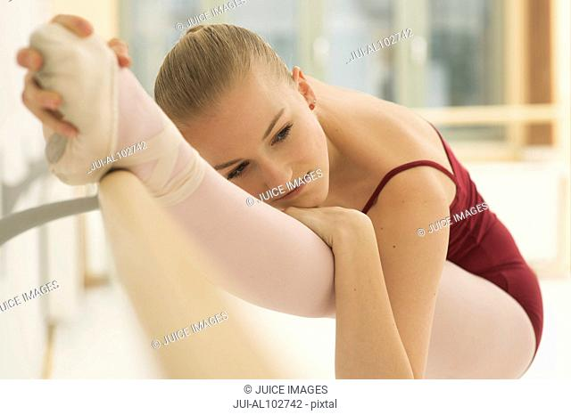 A ballet dancer stretching her leg on the barre