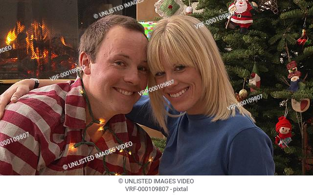 Couple wrapped in Christmas tree lights make eye contact with camera and then kiss / Bellevue, Idaho, United States