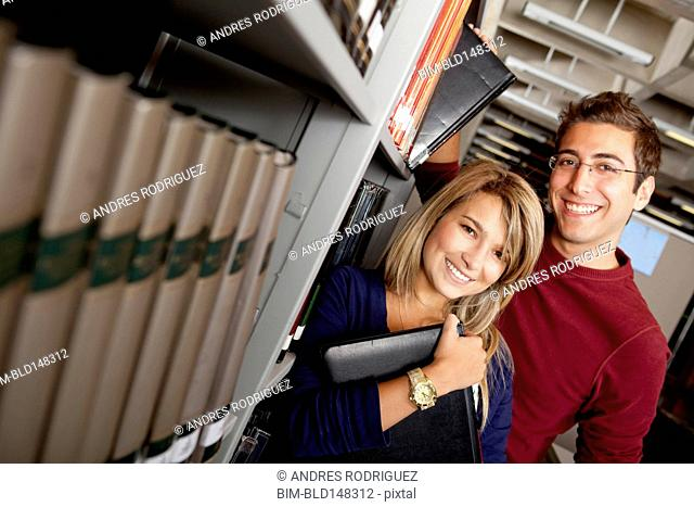 Hispanic couple standing together in library