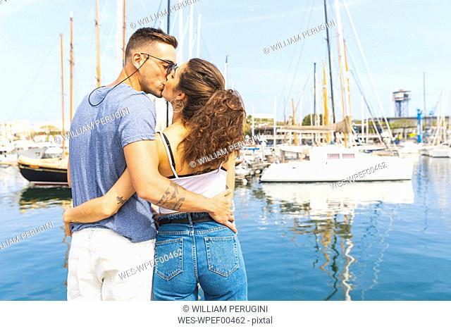 Back view of a young couple kissing at marina