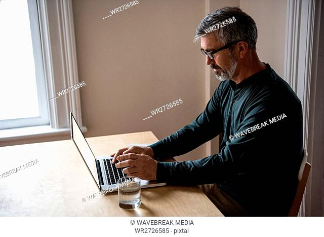 Man sitting at table and using laptop
