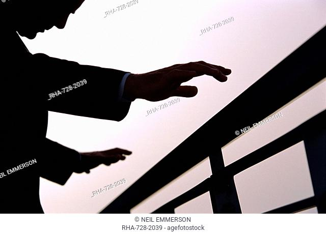 A business man outdoors with outstretched hands about to grasp railings
