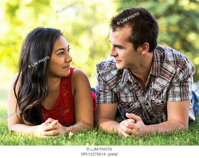 Mixed race couple spending quality time together in a park in autumn; St. Albert, Alberta, Canada