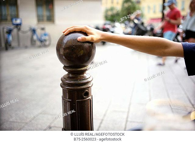 Closeup of hand and arm of a teenager leaning against a bollard of a street in Nice, Provence-Alpes-Cote Azur, France, Europe