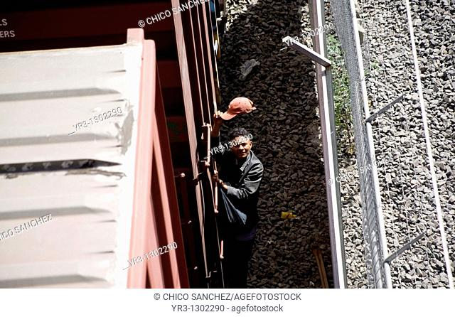 An undocumented Central American migrant traveling across Mexico to work in the United States salutes with his cap as he holds on a moving train in Mexico City