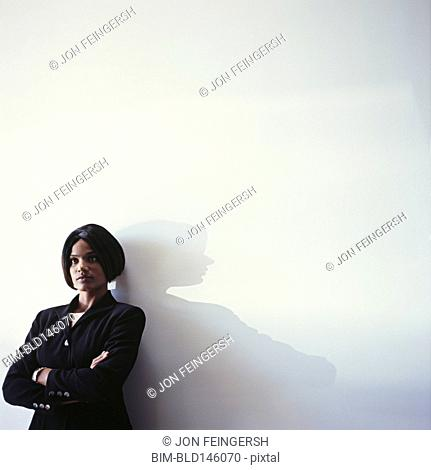 Serious businesswoman leaning against wall