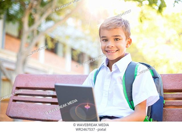Happy schoolboy sitting on bench with digital tablet