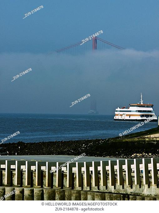 Ferry crossing river Tagus (Tejo) with April 25th bridge in fog, Lisbon, Portugal, western Europe