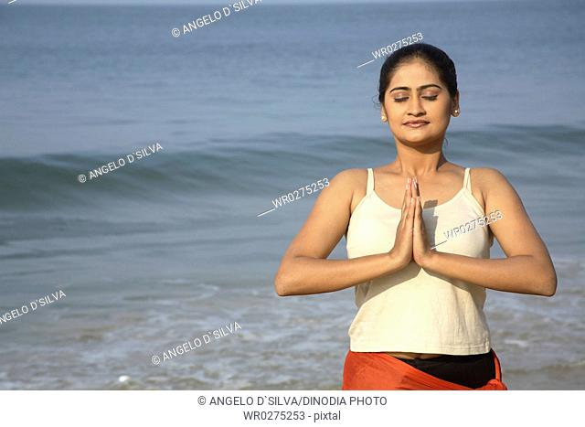 South Asian Indian young lady doing aerobics on seashore , Shiroda , Dist Sindhudurga , Maharashtra , India MR703E