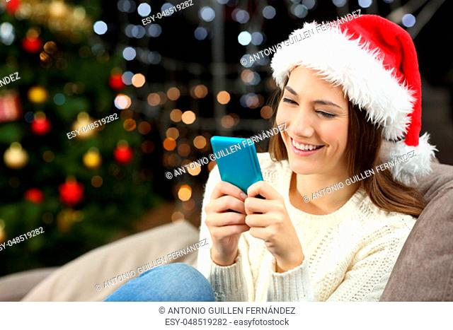 Happy woman texting on the phone in christmas sitting on a couch in the living room at home