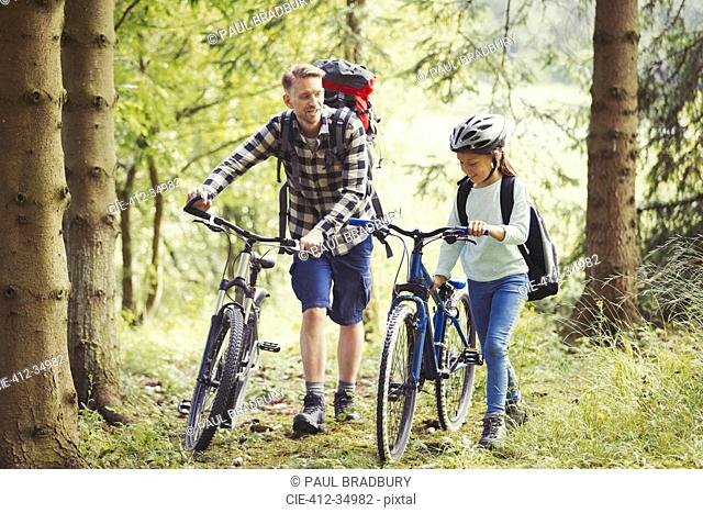 Father and daughter with backpacks walking mountain bikes in woods