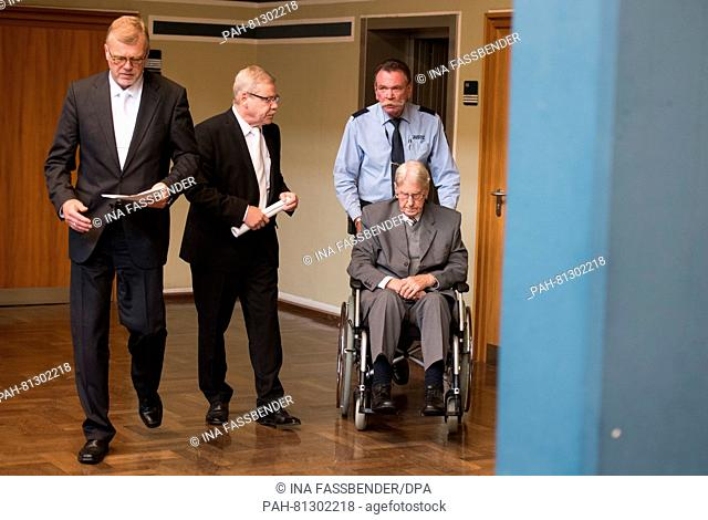 The former SS guard. Reinhold Hanning (m) is guided out of the courtroom with his lawyers Andreas Scharmer (m) and Johannes Salmen (l) in in a wheelchair at the...