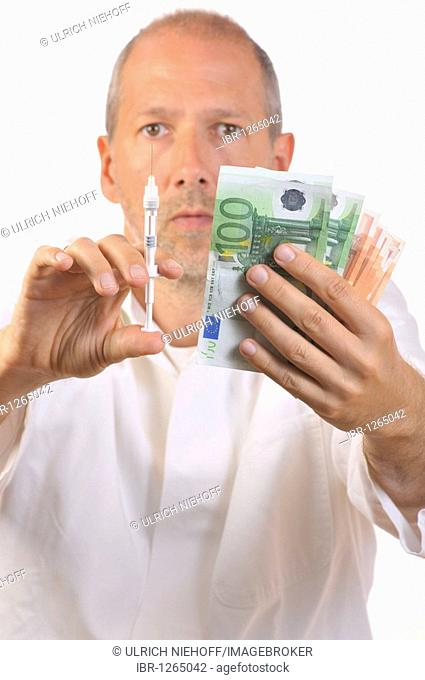 Doctor holding a syringe and banknotes