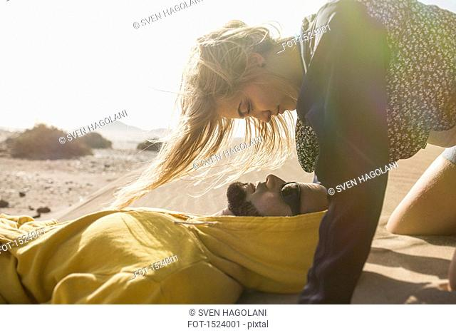Romantic young woman looking at man lying on sand